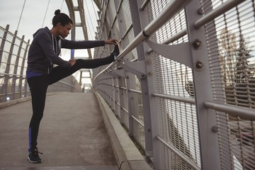 Woman stretching legs on railing at bridge