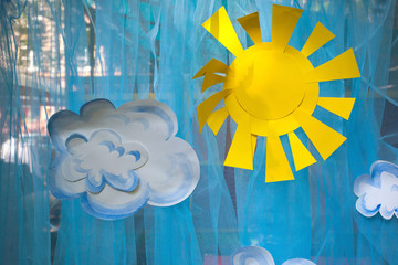 The decorations of appliques, paper sun and clouds