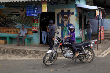 A boy plays with his father's motorbike at the central park in Nueva Trinidad