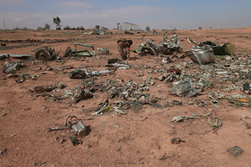 A Syrian Democratic Forces (SDF) fighter inspects destroyed airplane parts inside Tabqa military airport after taking control of it from Islamic State fighters, west of Raqqa city