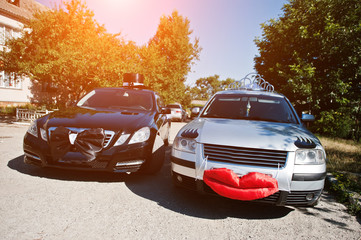 Funny wedding car with lips and eyelashes for bride, and with bow tie and hat for groom.