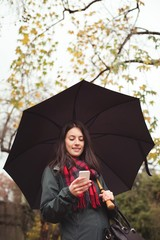 Woman using mobile phone while holding umbrella