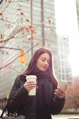 Woman holding coffee cup while using smartphone