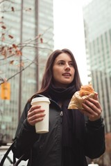 Woman looking away while holding food and drink