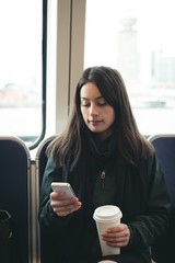 Woman using smart phone while sitting in train