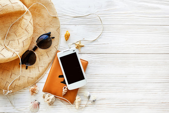 summer travel vacation concept flat lay, space for text.  passport plane hat  phone with empty screen and sunglasses and shells on white wooden background. hello summer. wanderlust