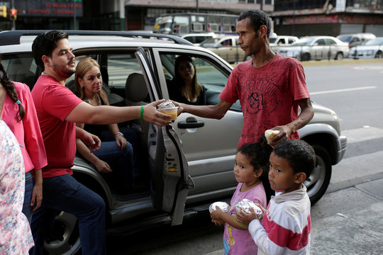Diego Prada, volunteer of the Make The Difference (Haz La Diferencia) charity initiative, gives a cup of soup and an arepa to a man in a street of Caracas