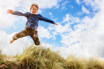 Boy leaping and jumping over sand dunes on beach vacation
