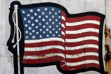 A worn and rusty painted picture of a U.S. flag is pictured on the side of a steel business in Peoria