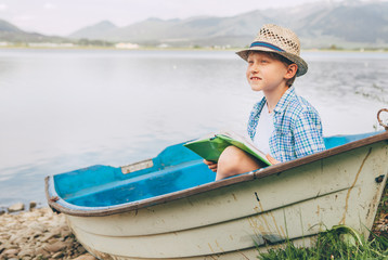 Dreaming boy with book sits in old boat on the mountain lake bank