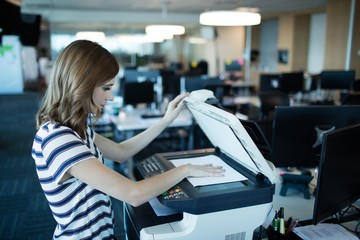 Businesswoman using copy machine in office Wall mural
