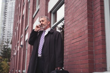 Businessman using mobile while standing against building
