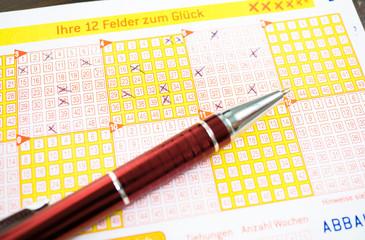 Ausgefüllter Lottoschein mit Kugelschreiber auf Holztisch