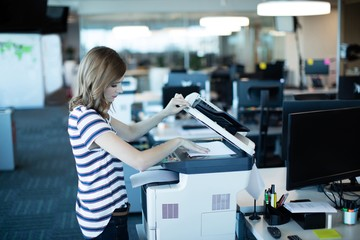 Young businesswoman using copy machine in office Wall mural