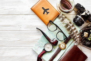 time to travel concept, hipster flat lay. map passport money compass and glasses photo camera pipe on white wooden background top view. planning vacation. space for text, wanderlust and explore.
