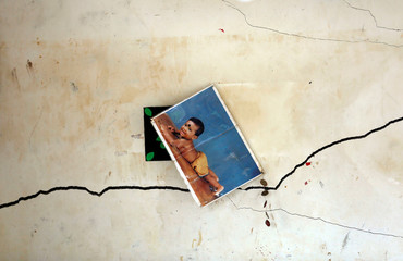 A photograph of a baby is seen on a cracked wall in a damaged house during a rescue mission after a garbage dump collapsed and buried dozens of houses in Colombo
