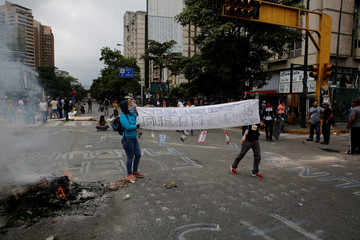 """Opposition supporters hold a placard that reads """"Venezuela wants democracy. Maduro out"""" as they attend a rally against Venezuela's President Maduro in Caracas"""