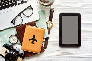 travel and wanderlust concept, planning summer vacation, space for text. tablet with empty screen, money map compass photo camera glasses wallet watch laptop on white wooden background