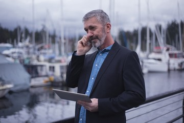 Businessman using smart phone by harbor