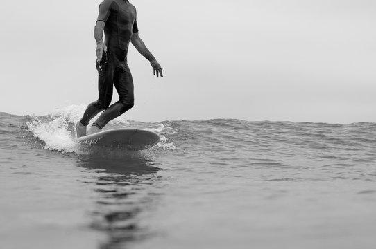 surfeur, surfer en longboard sur une vague en train de marcher noir et blanc à soulac sur mer