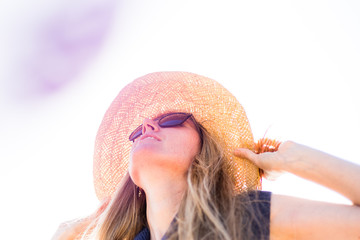 Young, blonde female, girl in a straw hat and black glasses on the sun. California. Spring