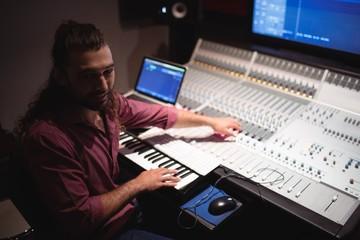 Male audio engineer playing electric keyboard