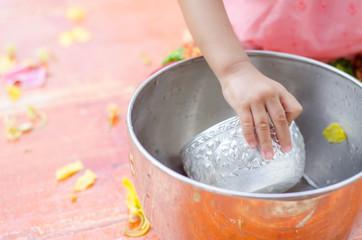 Asian toddler girl with traditional thai costumes enjoy splashing water during Thailand Water Festival (Songkran Day)