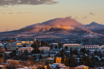 Small mountain town college lightly covered with snow at sunset