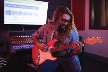 Male audio engineer playing electric guitar