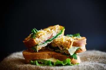 Fried hot sandwich with sausage and salad leaves