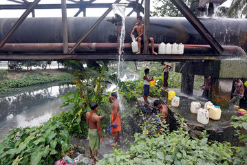 Residents bathe with water that is leaking from broken pipe valves in Kolkata