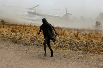 A boy moves away as a United Nations World Food Programme (WFP) helicopter lands in Rubkuai village, Unity State, northern South Sudan