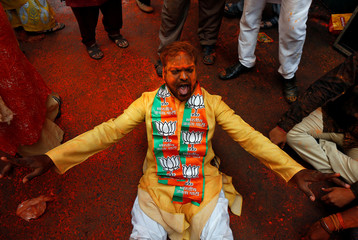 A supporter of the Bharatiya Janata Party (BJP) celebrates after learning of the initial poll results outside the party headquarters in Kolkata