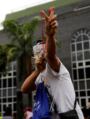 A demonstrator uses a slingshot while clashing with riot police during a rally against Venezuela's President Nicolas Maduro in Caracas