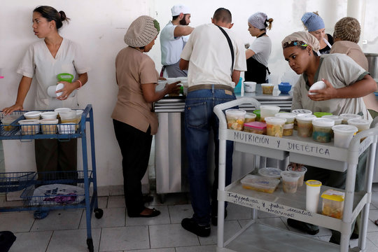 Waitresses of the J.M. de los Rios Children Hospital wait for cups of soup donated by La Casa Bistro restaurant to distribute them at hospitalization floors, in Caracas