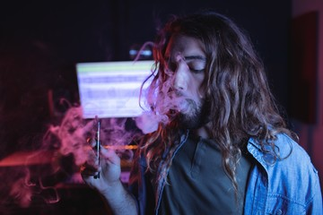 Male audio engineer smoking electronic cigarette
