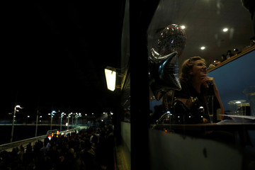 A woman looks up during a greyhound race break at Wimbledon Stadium in London