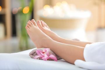 Female legs on massage table in beauty salon