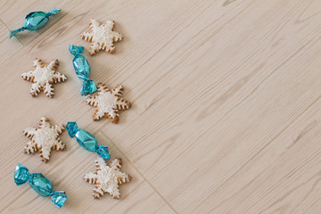 Gingerbread snowflake and bright candies on wood background. Aerial view. Copy space.