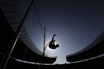 A pole vaulter is silhouetted against the sun during an athletics competition