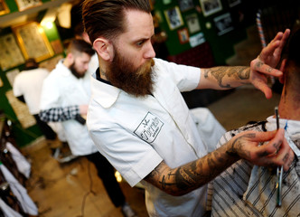 "Barber Alex ""Torreto"" Velios works on a gentleman's haircut at his Torreto barber shop in Frankfurt"