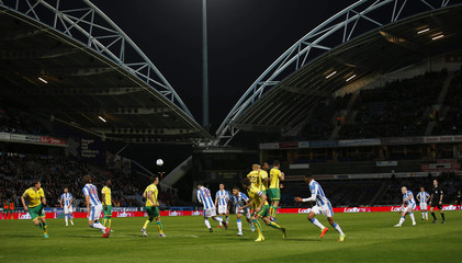 Huddersfield Town's Aaron Mooy (R) takes a free kick