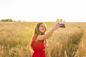 technology, summer holidays, vacation and people concept - smiling young woman taking selfie by smartphone on cereal field.