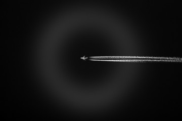 High flying jet with three jet trails lit up white against a dark black sky, atmospheric ring