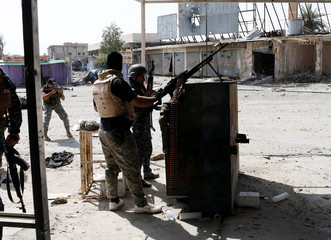 Iraqi federal police members fire their rifle at Islamic State fighters' positions during a battle at Jada district in western Mosul