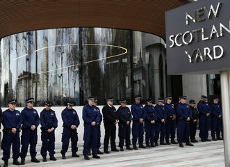 Police officers observe a moment's silence outside New Scotland Yard in Westminster the day after an attack, in London