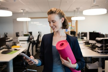Smiling businesswoman with exercise mat using mobile phone