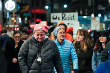 An off-duty police officer wearing a pink pussy protest hat joins other protesters as they walk through downtown Seattle during the Dress Like A Woman rally and march in Seattle, Washington