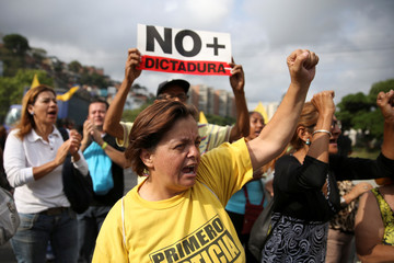 """Opposition supporters holding a placard that reads, """"No more dictatorship"""" shout slogans as they block a highway during a protest against Venezuelan President Nicolas Maduro's government in Caracas"""