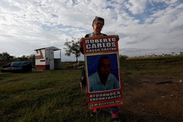 Rosalia Castro holds a poster with a picture of her missing son, Roberto Casso, as she stands by the gate to a plot of land where skulls were found at unmarked graves, on the outskirts of of Veracruz